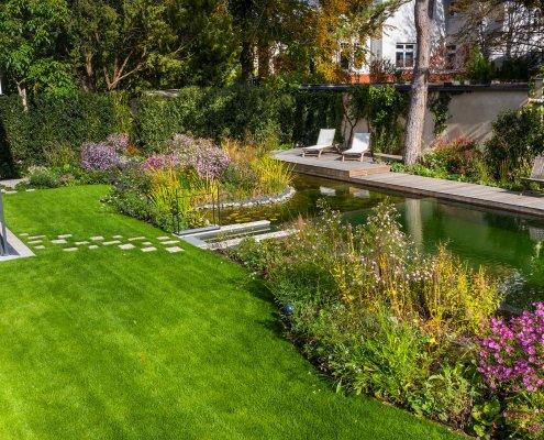 Garten mit Rasenfläche, Pflanzen und Schwimmteich